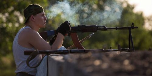 A pro-Russian militant smokes a cigarette as he takes his position preparing to fight against Ukrainian government troops at a checkpoint blocking the major highway which links Kharkiv, outside Slovyansk, eastern Ukraine, Friday, May 16, 2014. Outside the strategic city of Slovyansk, which has been the key stronghold of the pro-Russian insurgents for more than a month now, the armed separatists installed a new check-point on the eastern approaches of the city blocking the major highway which links Kharkiv, the capital of the neighboring region, and the Russian city of Rostov-on-Don across the border. (AP Photo/Alexander Zemlianichenko)