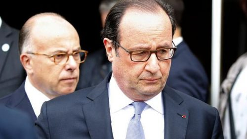 French President Francois Hollande (R) and Interior Minister Bernard Cazeneuve (L) leave the city hall after two assailants had taken five people hostage in the church at Saint-Etienne-du -Rouvray near Rouen in Normandy, France, July 26, 2016. Two attackers killed a priest with a blade and seriously wounded another hostage in a church in northern France on Tuesday before being shot dead by French police. REUTERS/Pascal Rossignol